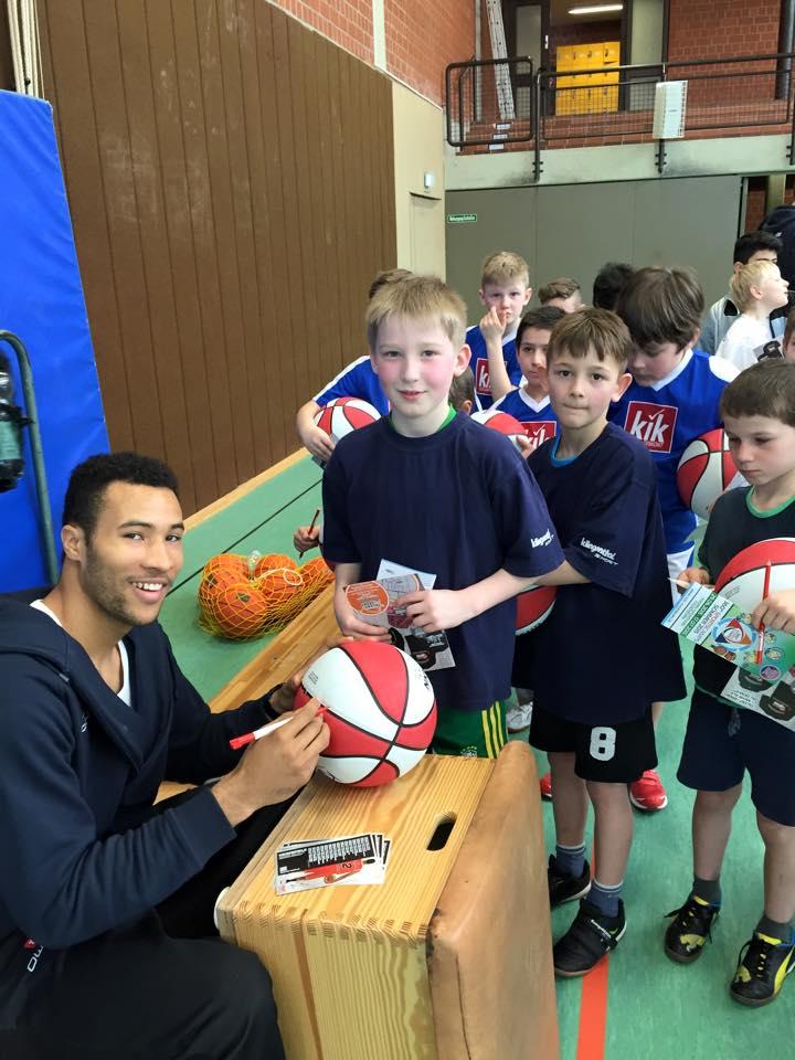 ProA-Spieler Reggie Willhite und Grundschüler hatten bei der ersten Vorrunde am 9. März sichtlich Spaß
