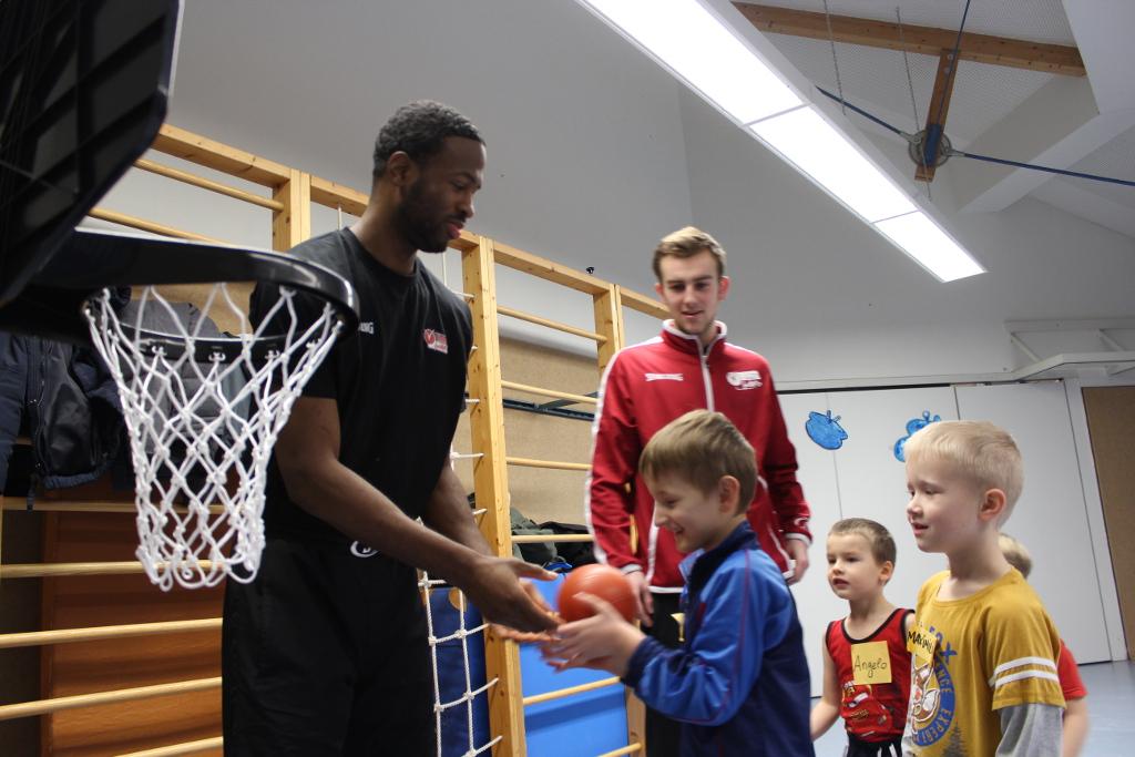 Ricky Taylor (l.), Janosch Krüger (hinten) und die Kinder weihen den neuen Minikorb ein